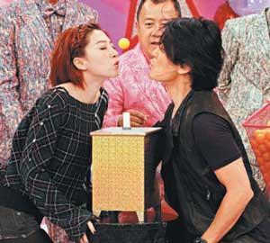 """郑伊健(右)与贾晓晨玩""""吹乒乓球""""时,保持距离。"""